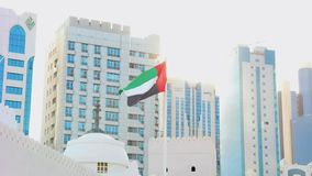 Τα Ηνωμένα Αραβικά Εμιράτα σημαιοστολίζουν τον κυματισμό γύρω από τον ορίζοντα πόλεων ενάντια στο λαμπρό ήλιο