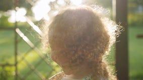 Τα θέτοντας παιχνίδια ήλιων στη σγουρή τρίχα ενός μικρού κοριτσιού φιλμ μικρού μήκους