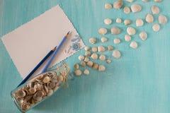 Τα θαλασσινά κοχύλια ανατρέπουν από το γυαλί μπουκαλιών, φύλλα του εγγράφου και της μάνδρας σε ένα μπλε υπόβαθρο Στοκ Εικόνες