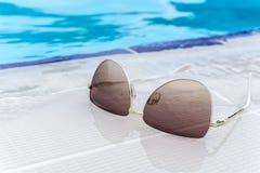 Τα θερινά γυαλιά ηλίου διαμορφώνουν την έννοια, γυαλιά ηλίου στην κολυμπώντας άκρη, υπαίθριο φως ημέρας Στοκ φωτογραφία με δικαίωμα ελεύθερης χρήσης