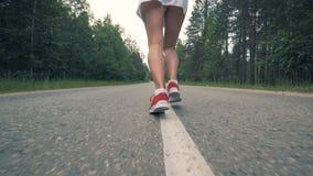 Τα θηλυκά πόδια στα πάνινα παπούτσια αρχίζουν να τρέχουν σε σε αργή κίνηση Υγιές λεπτό νέο τρέξιμο φιλάθλων απόθεμα βίντεο