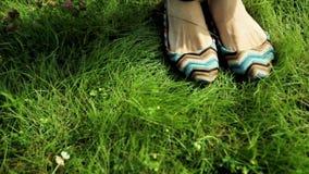 Τα θηλυκά πόδια στα παπούτσια θέτουν στην πράσινη χλόη απόθεμα βίντεο