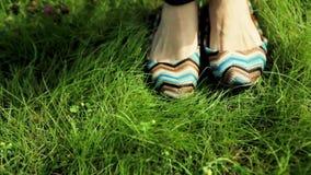 Τα θηλυκά πόδια στα παπούτσια θέτουν στην πράσινη χλόη φιλμ μικρού μήκους