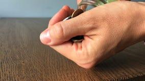 Τα θηλυκά χέρια ανοίγουν ένα βάζο και χύνουν έξω τα νομίσματα στον ξύλινο πίνακα Πλάγια όψη απόθεμα βίντεο