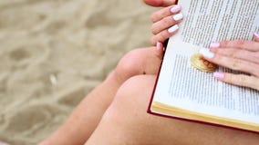 Τα θηλυκά χέρια ανοίγουν ένα βιβλίο και βρίσκουν bitcoin φιλμ μικρού μήκους