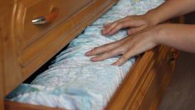 Τα θηλυκά χέρια απολυμαίνουν τις πάνες μωρών σε ένα ράφι, κινηματογράφηση σε πρώτο πλάνο φιλμ μικρού μήκους
