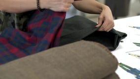 Τα θηλυκά χέρια βάζουν το ύφασμα σε έναν σωρό απόθεμα βίντεο