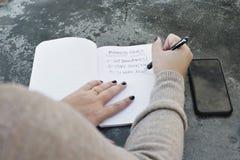 Τα θηλυκά χέρια γράφουν κάτω τους επιχειρησιακούς στόχους στοκ φωτογραφίες