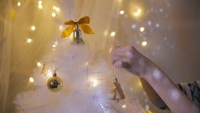 Τα θηλυκά χέρια διακοσμούν ένα δέντρο κάτω από τα φωτεινά φω'τα απόθεμα βίντεο