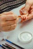 Τα θηλυκά χέρια κάνουν τις κούκλες BJD ή αναγεννημένος στον εργασιακό χώρο proce στοκ εικόνα