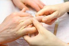 Τα θηλυκά χέρια κάνουν το μανικιούρ για το άτομο στοκ φωτογραφία με δικαίωμα ελεύθερης χρήσης