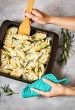 Τα θηλυκά χέρια κρατούν τα ιταλικά ζυμαρικά Conchiglioni Rigati που γεμίζεται με το τυρί και τα πράσινα στο συγκεκριμένο πίνακα στοκ εικόνα με δικαίωμα ελεύθερης χρήσης