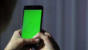 Τα θηλυκά χέρια κρατούν μια κινητή συσκευή με μια πράσινη οθόνη Κλειδί χρωμίου απόθεμα βίντεο