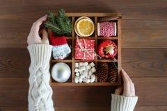 Τα θηλυκά χέρια κρατούν το ξύλινο κιβώτιο με τα αντικείμενα Χριστουγέννων Στοκ εικόνα με δικαίωμα ελεύθερης χρήσης