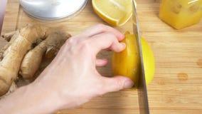 Τα θηλυκά χέρια κόβουν ένα μαχαίρι με το λεμόνι για ένα ποτό που γίνεται από τα εσπεριδοειδή χειροποίητα με τη ρίζα πιπεροριζών 4 απόθεμα βίντεο