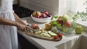Τα θηλυκά χέρια κόβουν το μήλο στις φέτες για μια σαλάτα φρούτων για το πρόγευμα στην κουζίνα το πρωί Προετοιμασία απόθεμα βίντεο