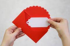 Τα θηλυκά χέρια παίρνουν έξω μια επιστολή από έναν κόκκινο φάκελο Valentine& x27 s Στοκ φωτογραφία με δικαίωμα ελεύθερης χρήσης