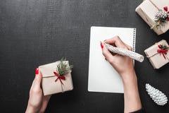 Τα θηλυκά χέρια που γράφουν την επιστολή Χριστουγέννων με το επίπεδο δώρων και διακοσμήσεων βάζουν, τοπ άποψη Χριστούγεννα και νέ Στοκ Φωτογραφία