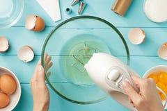 Τα θηλυκά χέρια που κτυπούν τα λευκά αυγών αποβουτυρώνουν με τον αναμίκτη στο κύπελλο στον μπλε ξύλινο πίνακα στοκ φωτογραφία