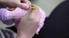 Τα θηλυκά χέρια ράβουν μια teddy αρκούδα Δημιουργία των μαλακών χειροποίητων παιχνιδιών Βιντεοσκοπημένες εικόνες απόθεμα βίντεο