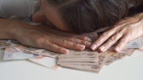 Τα θηλυκά χέρια συλλέγουν πολλά χρήματα σε έναν άσπρο πίνακα, ταϊλανδικά τραπεζογραμμάτια, ρωσικά τραπεζογραμμάτια στοκ εικόνα
