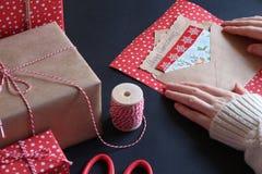 Τα θηλυκά χέρια συσκευάζονται την επιστολή Χριστουγέννων σε έναν φάκελο Στοκ Εικόνες