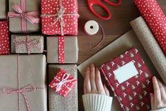 Τα θηλυκά χέρια συσκευάζουν το βιβλίο Χριστουγέννων στο έγγραφο Στοκ Εικόνες