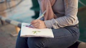 Τα θηλυκά χέρια σύρουν τα λουλούδια σε ένα sketchbook, εξωτερικό κινηματογραφήσεων σε πρώτο πλάνο κοντά στη θάλασσα φιλμ μικρού μήκους