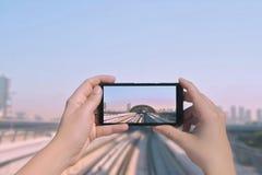 Τα θηλυκά χέρια ` s παίρνουν μια εικόνα του μονοτρόχιου σιδηροδρόμου και των ουρανοξυστών του Ντουμπάι στο κινητό τηλέφωνο Εικόνα Στοκ Φωτογραφίες