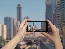 Τα θηλυκά χέρια ` s παίρνουν μια εικόνα του μονοτρόχιου σιδηροδρόμου και των ουρανοξυστών του Ντουμπάι στο κινητό τηλέφωνο Εικόνα Στοκ Εικόνες