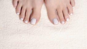 Τα θηλυκά toe με το άσπρο pedicure στην πετσέτα υφασμάτων ελεφαντόδοντου, κλείνουν επάνω Γυμνά πόδια γυναικών στοκ εικόνα