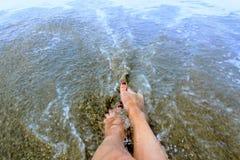 Τα θηλυκά πόδια βρίσκονται στην άμμο στη ζώνη κυματωγών Στοκ Εικόνες