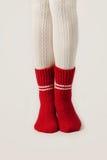 Τα θηλυκά πόδια στις άσπρες γυναικείες κάλτσες και το κόκκινο πλέκουν τις κάλτσες Στοκ Εικόνα