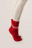 Τα θηλυκά πόδια στις άσπρες γυναικείες κάλτσες και το κόκκινο πλέκουν τις κάλτσες Στοκ Εικόνες