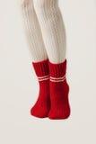 Τα θηλυκά πόδια στις άσπρες γυναικείες κάλτσες και το κόκκινο πλέκουν τις κάλτσες Στοκ εικόνα με δικαίωμα ελεύθερης χρήσης