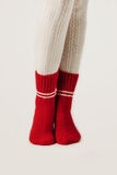 Τα θηλυκά πόδια στις άσπρες γυναικείες κάλτσες και το κόκκινο πλέκουν τις κάλτσες Στοκ Φωτογραφίες