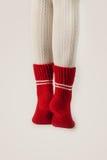 Τα θηλυκά πόδια στις άσπρες γυναικείες κάλτσες και το κόκκινο πλέκουν τις κάλτσες Στοκ φωτογραφία με δικαίωμα ελεύθερης χρήσης