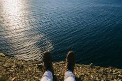 Τα θηλυκά πόδια στις μπότες δέρματος είναι στην άκρη ενός απότομου βράχου Στοκ φωτογραφία με δικαίωμα ελεύθερης χρήσης