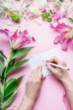 Τα θηλυκά χέρια γράφουν με τη ευχετήρια κάρτα μολυβιών στο κενό τυλίγουν στο ρόδινο επιτραπέζιο υπόβαθρο με τα λουλούδια κρίνων κ Στοκ Εικόνες