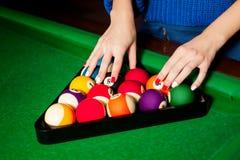 Τα θηλυκά χέρια είναι τακτοποιημένες σφαίρες μπιλιάρδου στο τρίγωνο Στοκ φωτογραφία με δικαίωμα ελεύθερης χρήσης