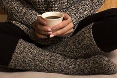 Τα θηλυκά χέρια κρατούν ένα φλυτζάνι καφέ και ένα παλαιό ανοικτό βιβλίο Στοκ Εικόνες
