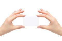 Τα θηλυκά χέρια κρατούν την άσπρη κάρτα σε ένα άσπρο υπόβαθρο Στοκ εικόνες με δικαίωμα ελεύθερης χρήσης