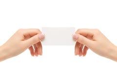 Τα θηλυκά χέρια κρατούν την άσπρη κάρτα σε ένα άσπρο υπόβαθρο Στοκ φωτογραφία με δικαίωμα ελεύθερης χρήσης