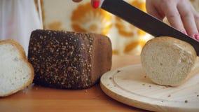Τα θηλυκά χέρια κόβουν το γαλλικό μαχαίρι ψωμιού σε έναν ξύλινο απόθεμα βίντεο