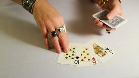 Τα θηλυκά χέρια με τα χρυσά κοσμήματα σχεδιάζουν τις κάρτες παιχνιδιού φιλμ μικρού μήκους
