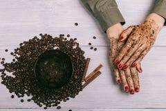 Τα θηλυκά χέρια με την κόκκινη στιλβωτική ουσία καρφιών και τον εφαρμοσμένο καφέ τρίβουν στο θόριο Στοκ εικόνα με δικαίωμα ελεύθερης χρήσης