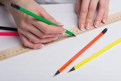 Τα θηλυκά χέρια με το κλασσικό γαλλικό μανικιούρ επισύρουν την προσοχή ένα μολύβι με τη βοήθεια ενός κυβερνήτη στο καθαρό τυποποι Στοκ Φωτογραφία