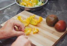 Τα θηλυκά χέρια μιας ηλικιωμένης γυναίκας κόβουν το πιπέρι για τη σαλάτα Στοκ Φωτογραφία