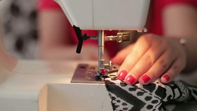 Τα θηλυκά χέρια που ράβουν τη χρήση η ράβοντας μηχανή, κλείνουν επάνω απόθεμα βίντεο