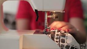 Τα θηλυκά χέρια που ράβουν τη χρήση η ράβοντας μηχανή, κλείνουν επάνω φιλμ μικρού μήκους